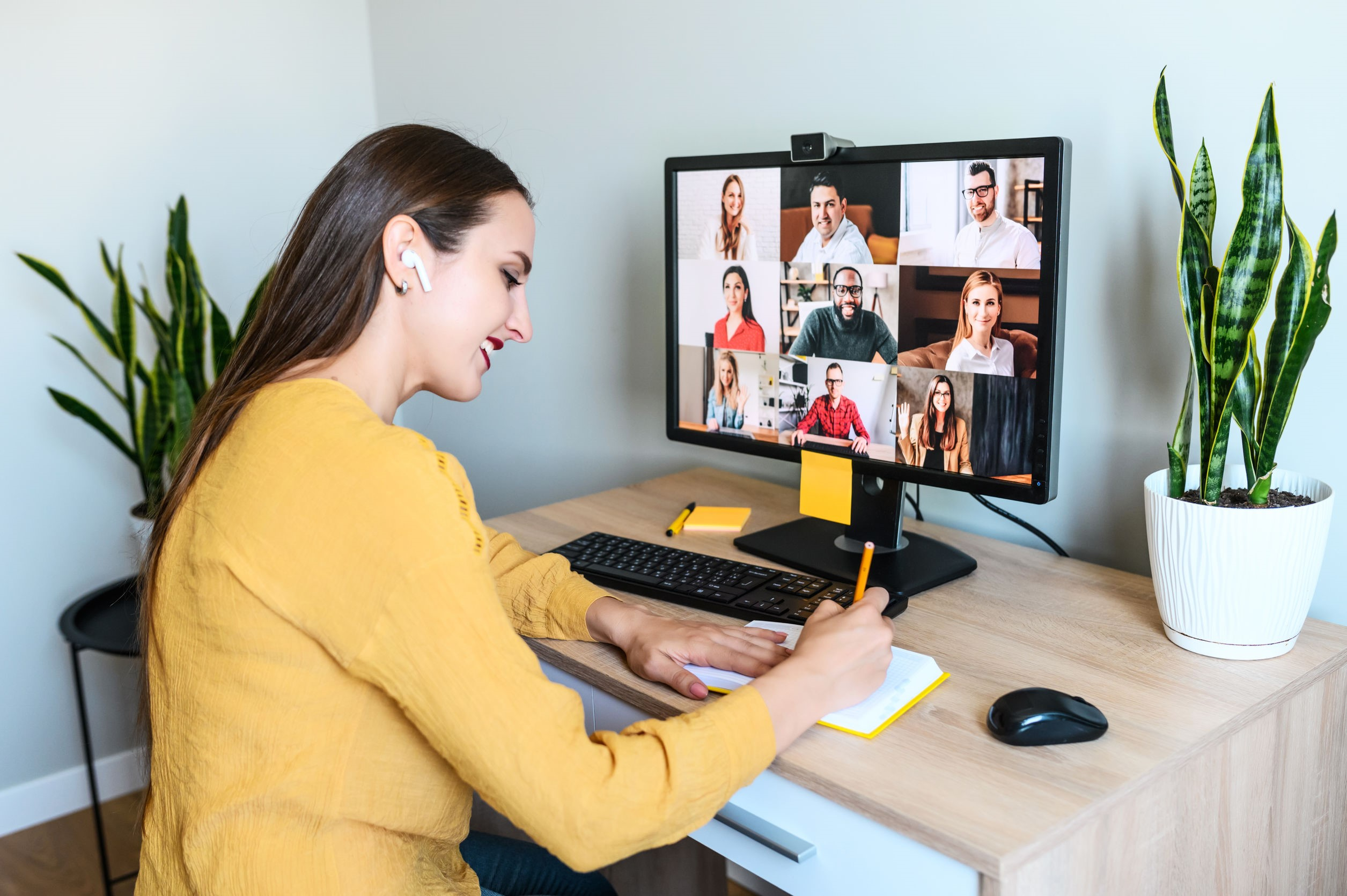 Smiling female sat at desk with monitor screen